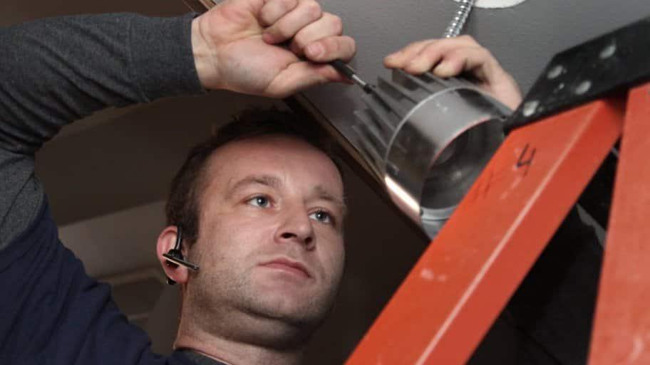 an electrician installing a light