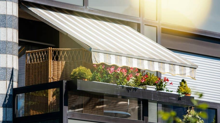 Beautiful balcony with flowers and retractable awnings