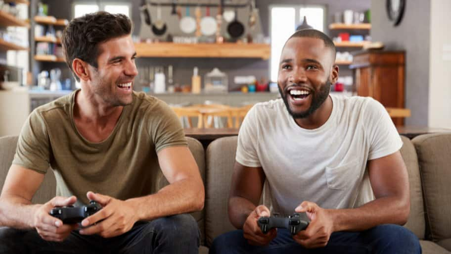 Two friends playing video games in basement