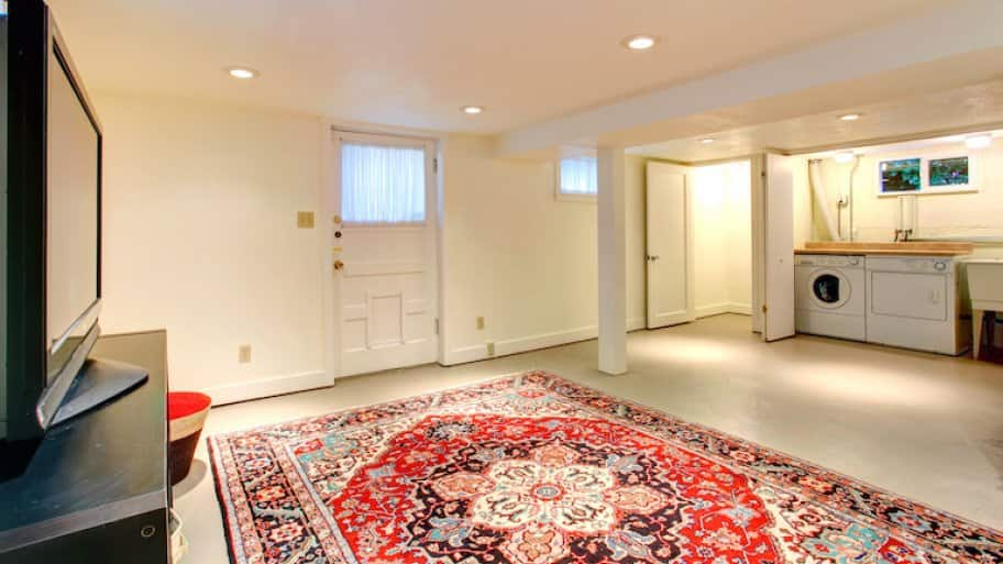 a bright basement with recessed lighting and large vintage rug (Photo by Iriana Shiyan - stock.adobe.com)