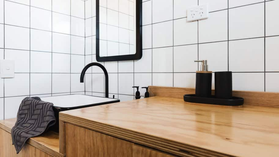 A bathroom with wooden vanity and black basin