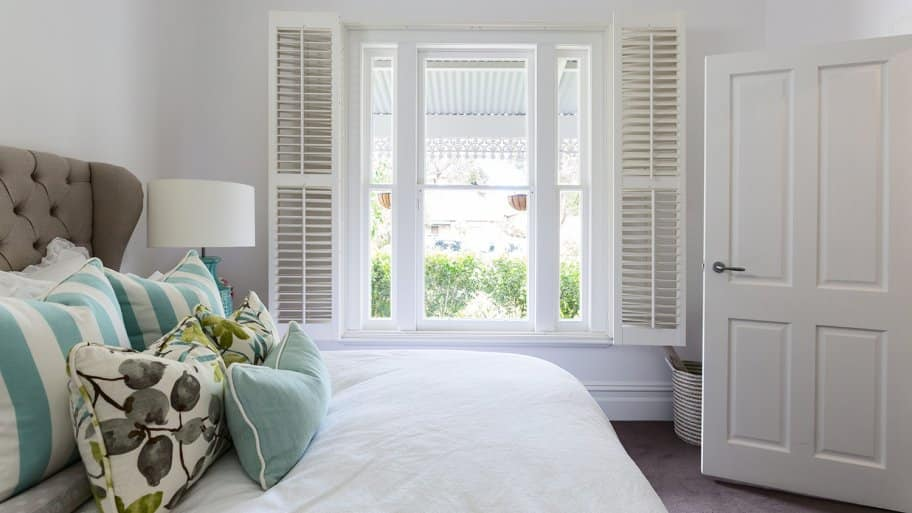 Bedroom with shutters at window