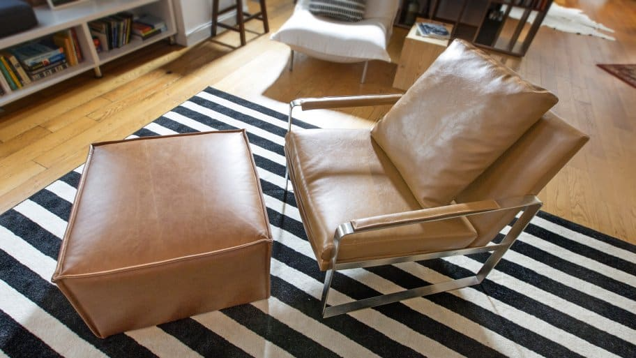 leather chair on black, white striped area rug (Photo by Frank Espich)