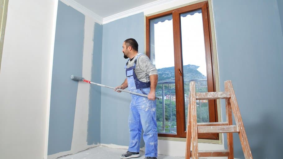 Painter at work painting room blue