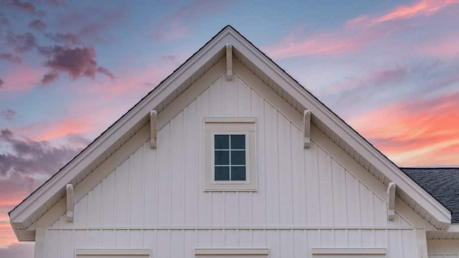 A house with a board and batten siding in sunset