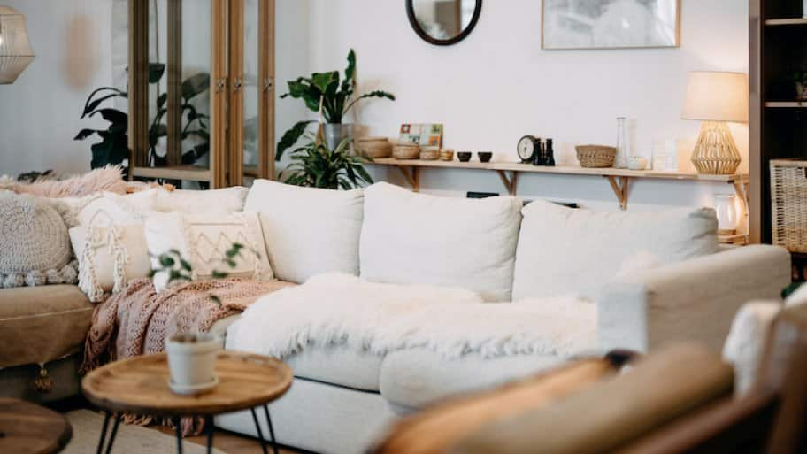 living room interior featuring light cream and tan wood tones with black accents and cozy, soft lighting