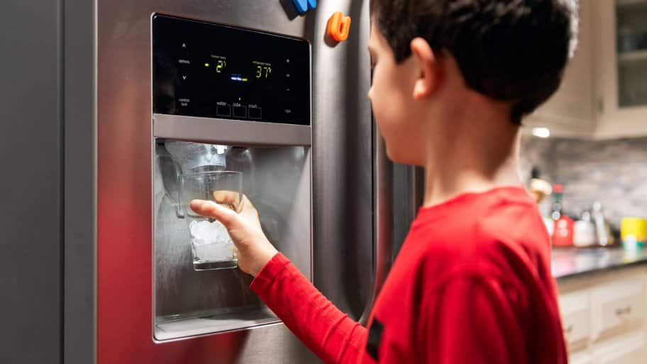 Boy getting ice from refrigerator