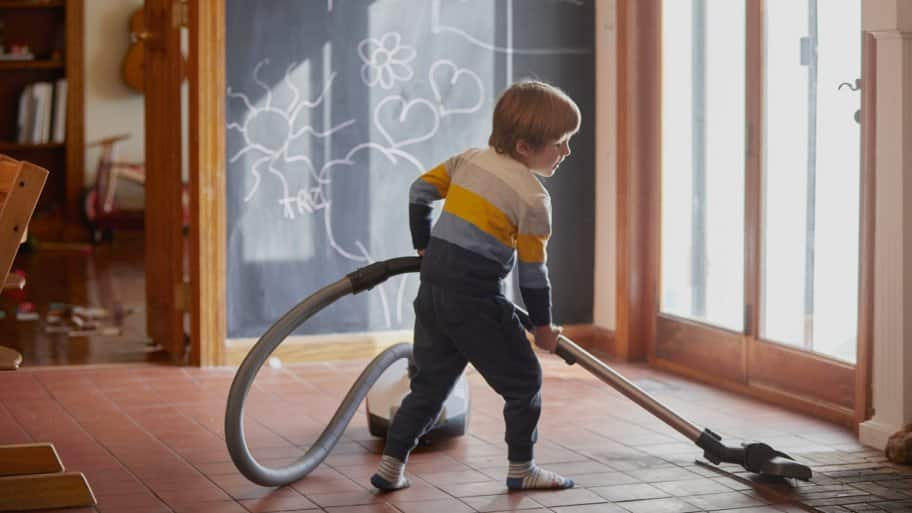 A boy with a vacuum in a room with ceramic tiles for flooring