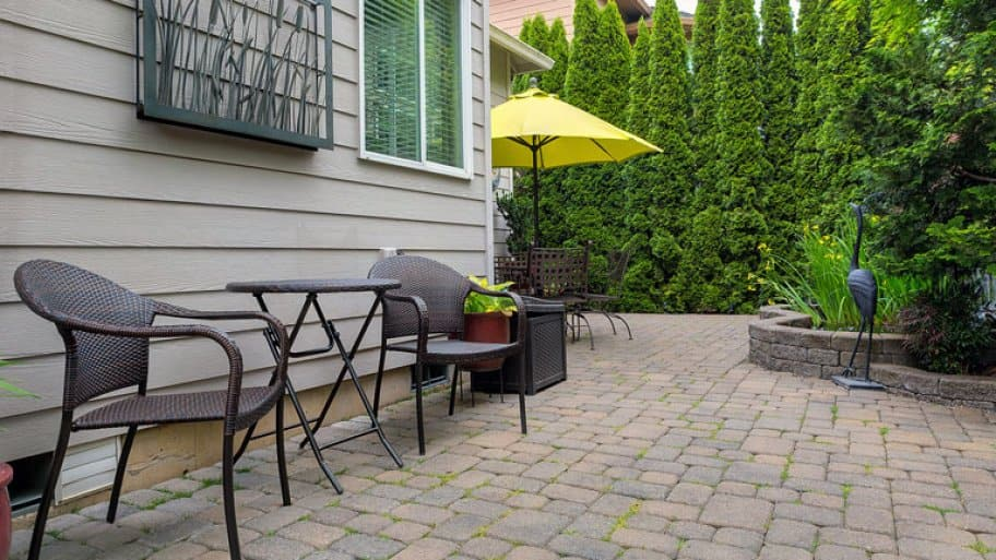 Backyard patio with chairs and table on brick pavers