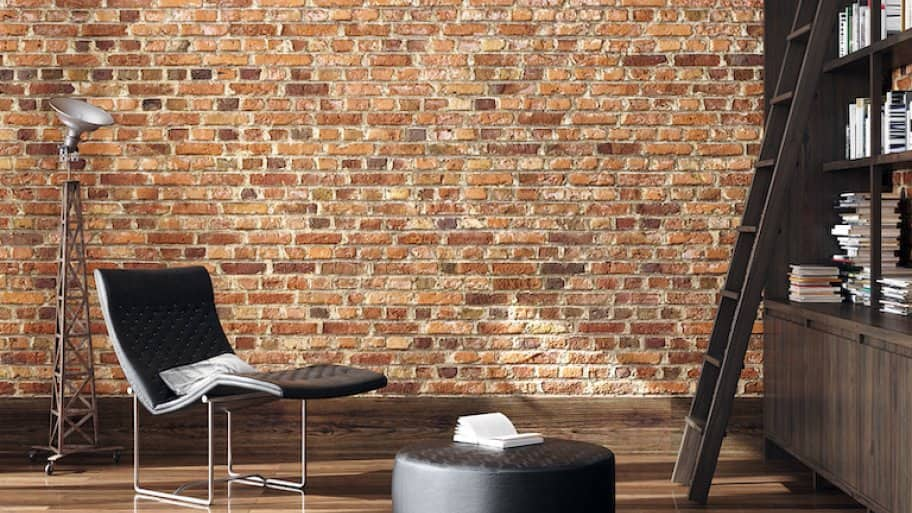 a brick wall and wood floor room with black modern reading chair and lamp, ottoman, and bookshelf with ladder