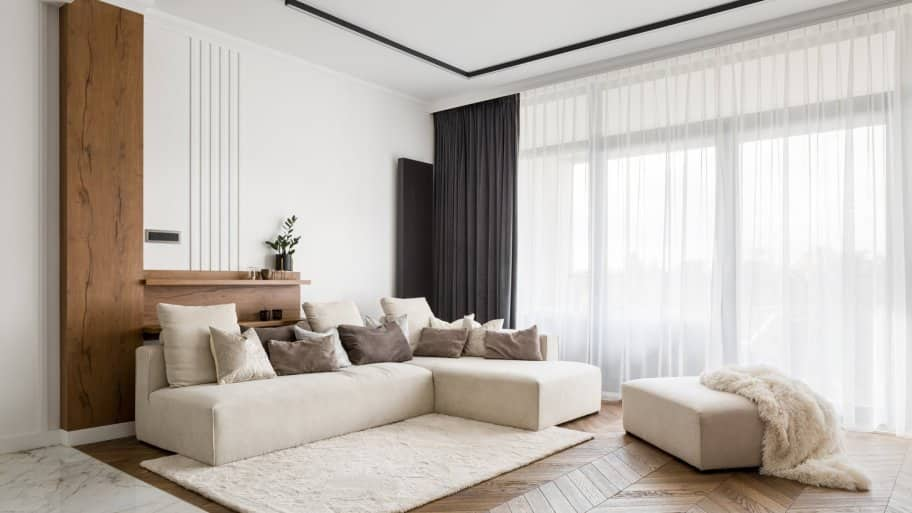 A bright living room with a tall windows and beautiful long curtains