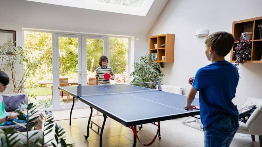 Two brothers playing ping pong in house's game room