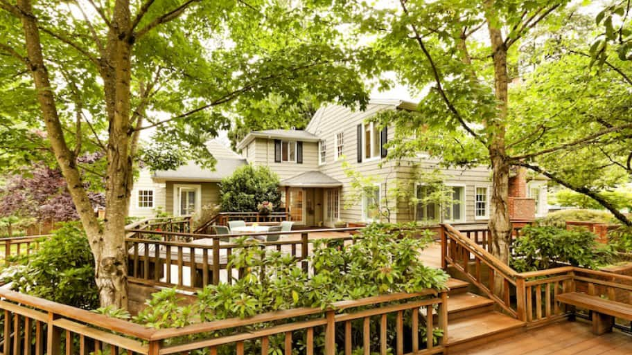 a large brown deck interspersed with bushes and trees in the backyard of a large white house