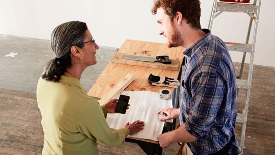 Carpenter showing blueprint to client