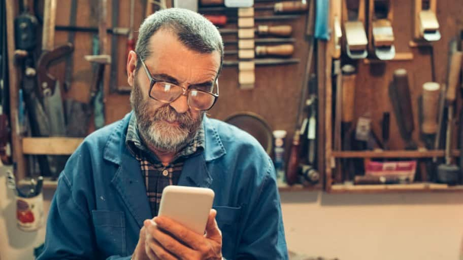 Senior man with beard in the workshop text messaging on mobile