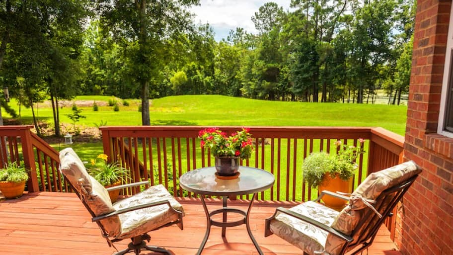 a cedar deck with two patio chairs and a small table overlooking a lush green yard