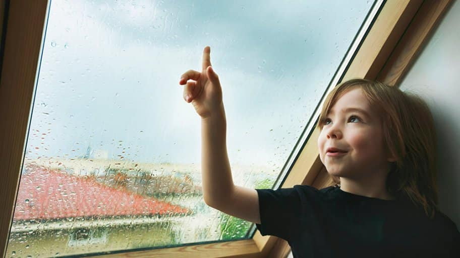 Child watching the rain from a rooftop window (Photo by portishead1/E+ via Getty Images)