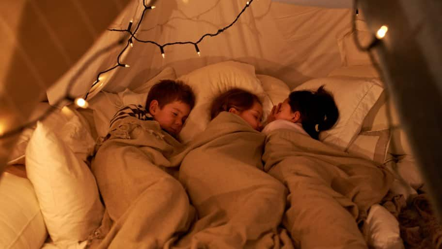 Three children sleeping together covered in a blanket
