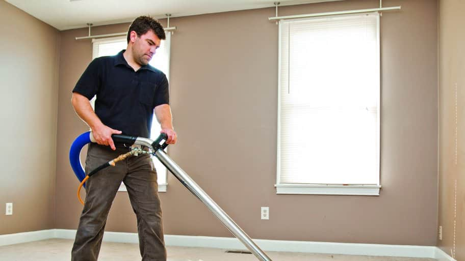 Chris Stone cleans carpets at a Northwest Indianapolis home. (Photo by Brandon Smith)
