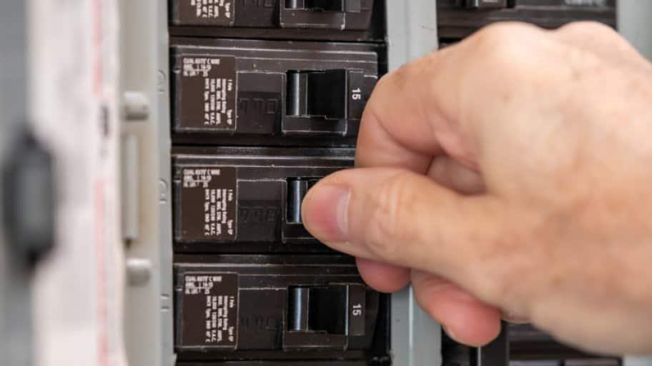 Man turning switch on circuit breaker