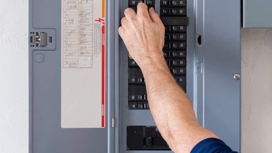 hand adjusting circuit breaker in home (Photo by © The Toidi - stock.adobe.com)