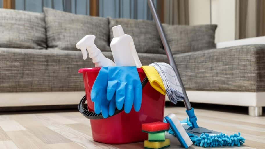bucket of cleaning supplies sits on light wood floor in front of grey couch
