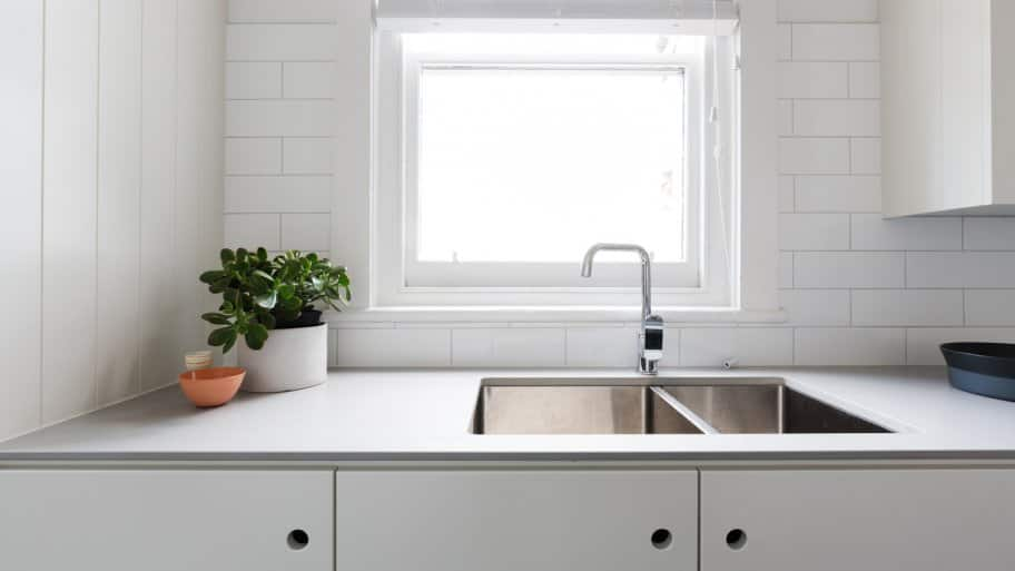 A contemporary white kitchen with laminate countertop