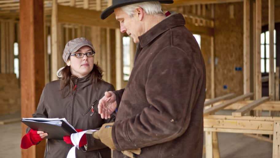 homeowner talks to contractor in unfinished new home