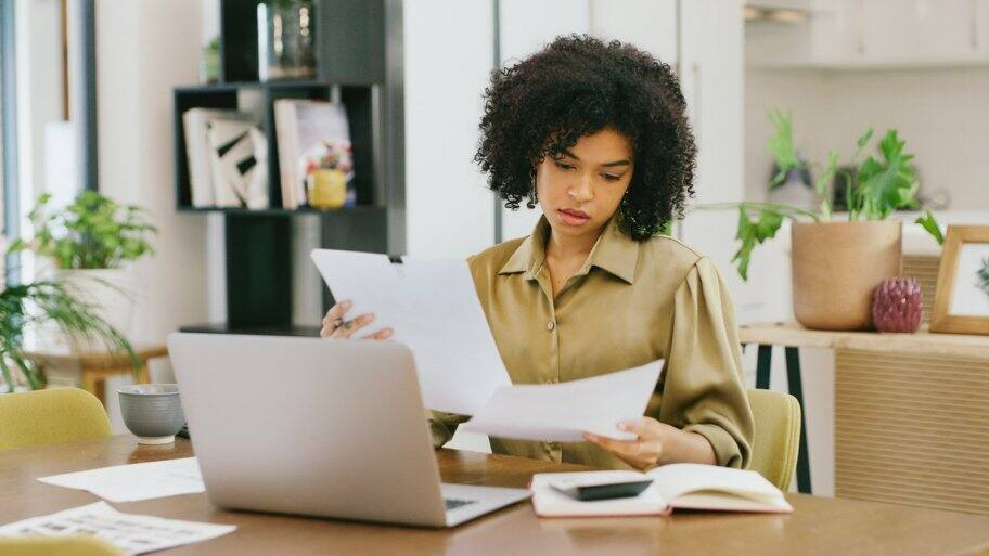 A contractor checking her papers while doing a cost estimate
