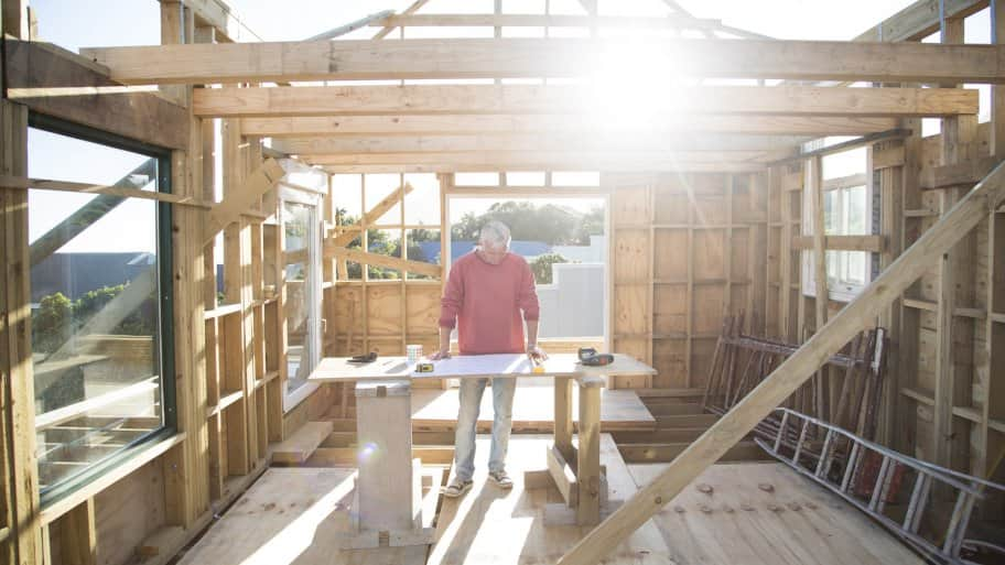 contractor stands at work table in a new house being built