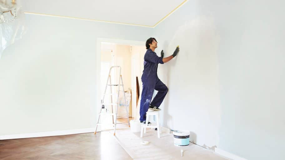 A contractor standing on a ladder while applying plaster on wall