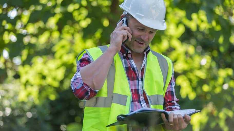 Contractor talks on phone to a client