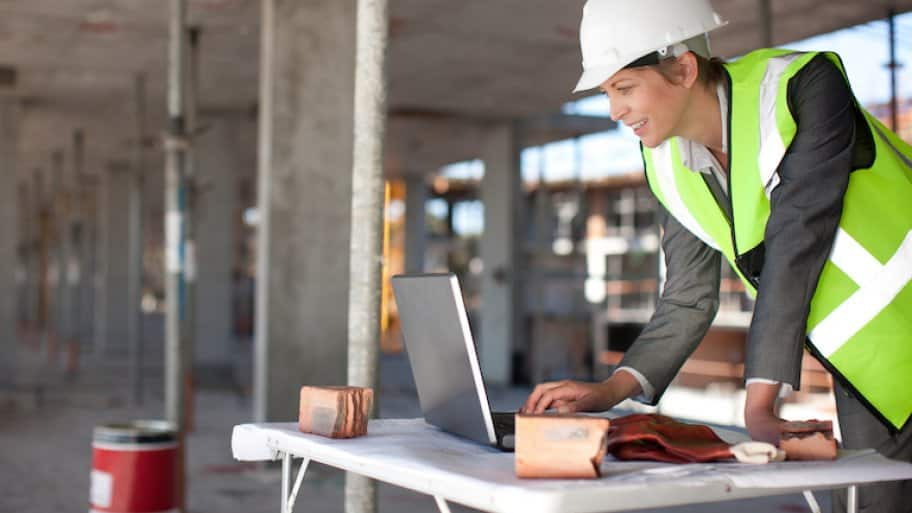 woman in contractor vest smiles at laptop on work table in warehouse