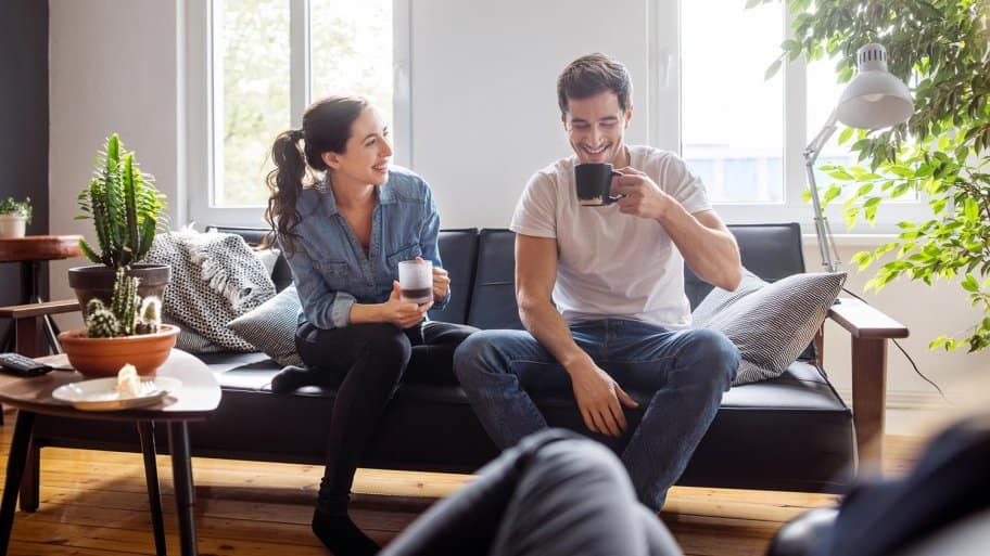 Couple drink coffee in their living room (Photo by Luis Alvarez / DigitalVision via Getty Images)
