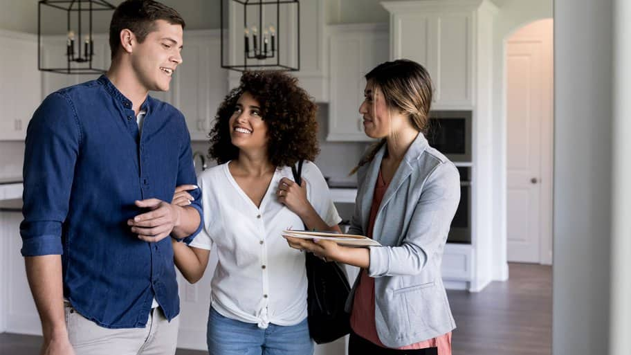 realtor showing couple apartment