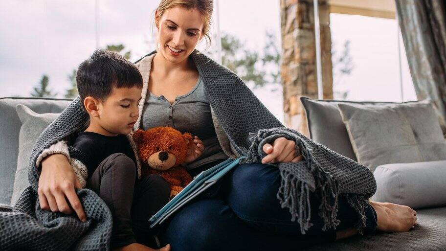 Mom and child read under blanket