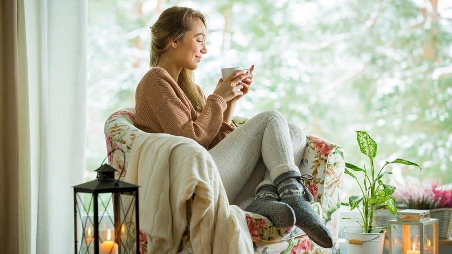Woman with coffee and blanket in cozy room (Photo by Aleksandra Suzi - stock.adobe.com)
