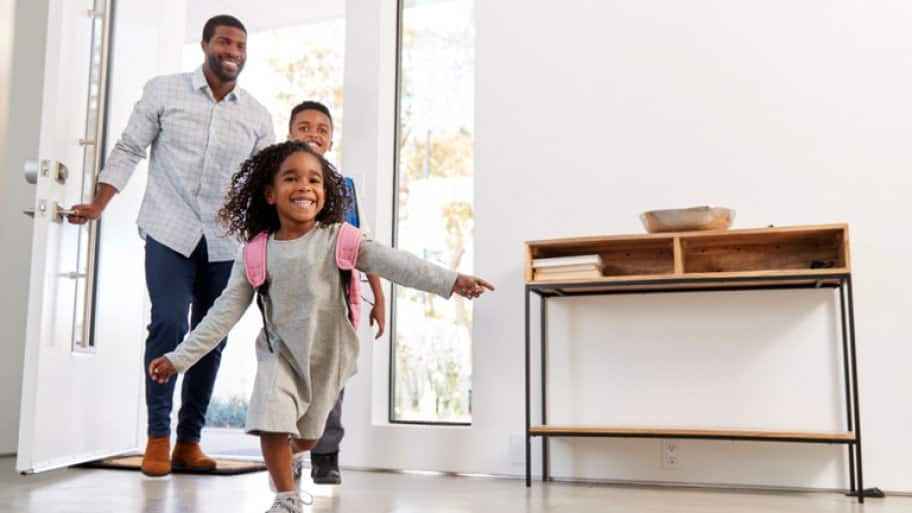 father, daughter and son arriving home through front door
