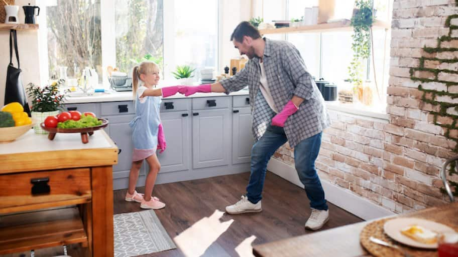 daughter and father fist bump with pink gloves and smile as they prepare to clean the kitchen