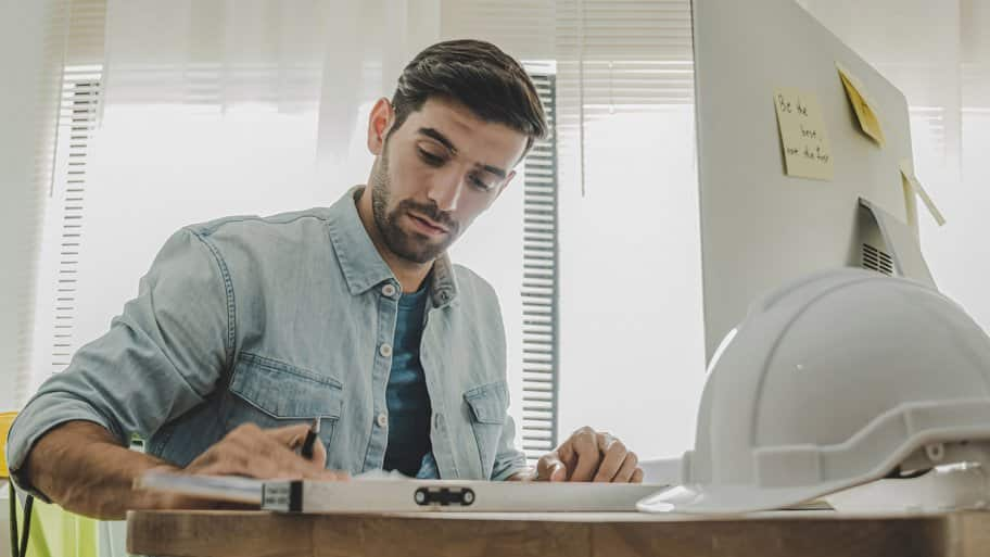 Contractor works on paperwork at desk