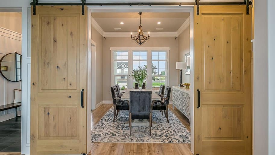 Modern dining room with a double barn door entrance (Photo by PC Photography/iStock/Getty Images Plus via Getty Images)