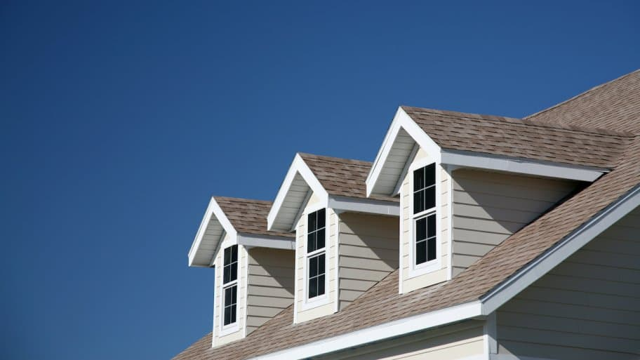three dormer windows with blue sky in background