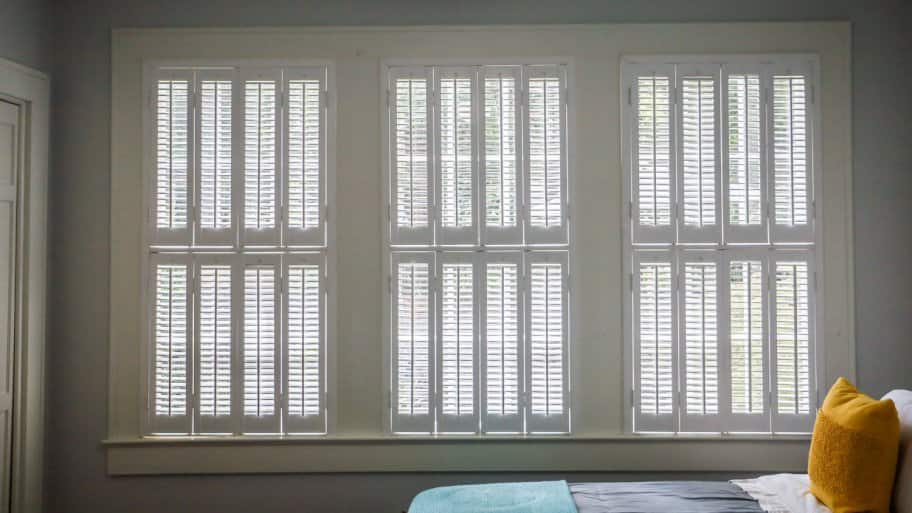 Three large windows with estate shutters in a bedroom
