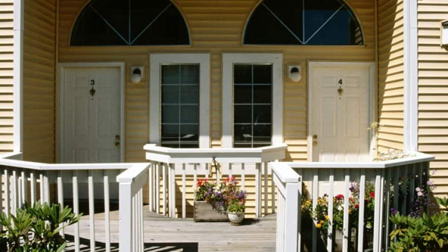 exterior front porch of duplex home, two doors