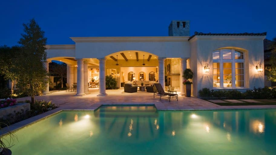 The exterior of a villa with lanterns on the walls and a lit swimming pool (Photo by moodboard/moodboard / Getty Images Plus via Getty Images)