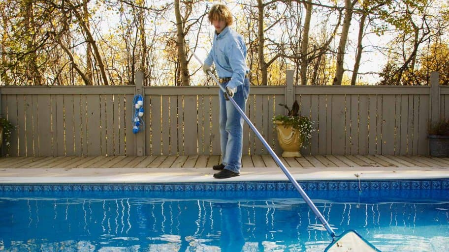 Man cleans fall leaves from pool