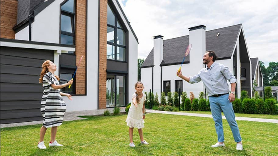 Family plays badminton in front of house