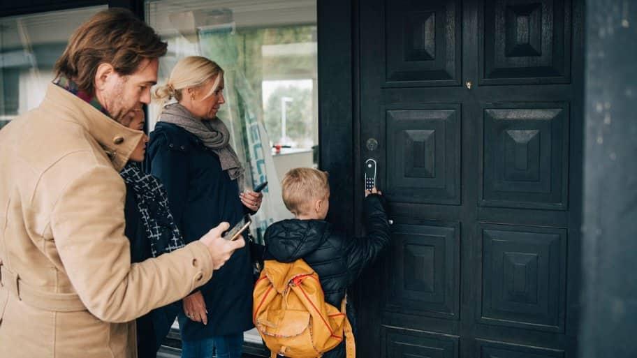 Son unlocks smart lock on door as family looks on