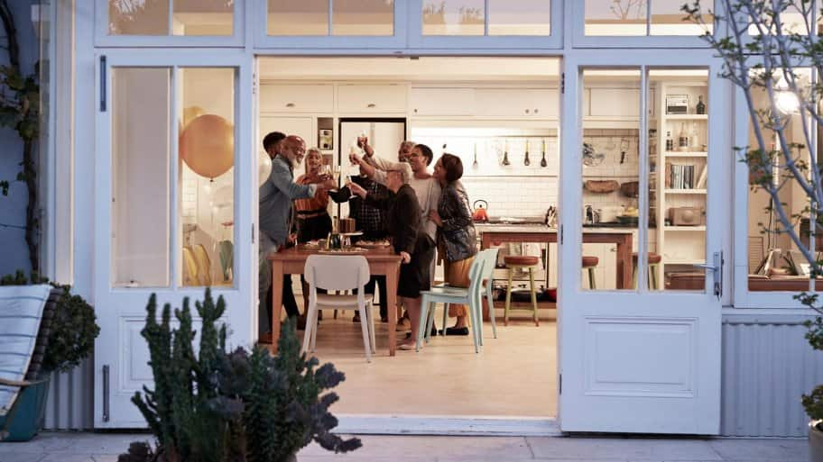 A family toasting at a birthday dinner in an open-plan kitchen (Photo by Klaus Vedfelt/DigitalVision via Getty Images)