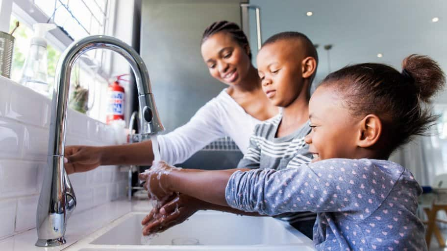 A mother and her children washing their hands together